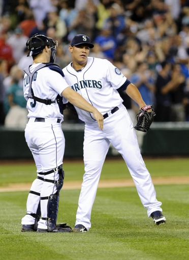 Jul 13, 2013; Seattle, WA, USA; Seattle Mariners catcher Mike Zunino (3) and Seattle Mariners relief pitcher Yoervis Medina (31) hug after the final out against the Los Angeles Angels during the 9th inning at Safeco Field. Seattle defeated Los Angeles 6-0. Mandatory Credit: Steven Bisig-USA TODAY Sports
