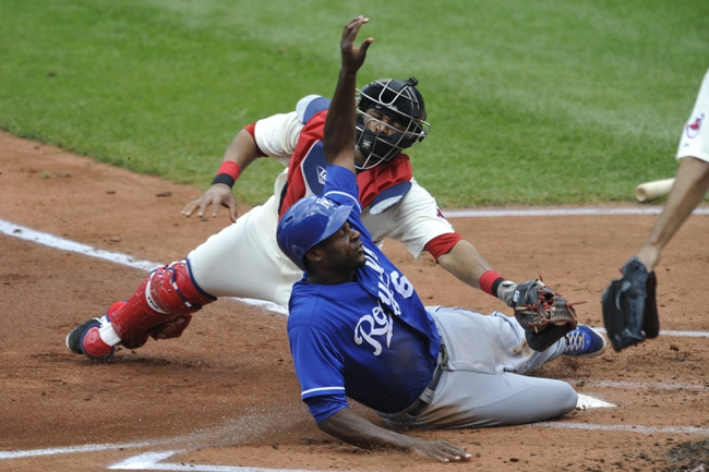Jul 14, 2013; Cleveland, OH, USA; Kansas City Royals center fielder Lorenzo Cain (6) scores before a tag attempt by Cleveland Indians catcher Carlos Santana (41) in the second inning at Progressive Field. Mandatory Credit: David Richard-USA TODAY Sports