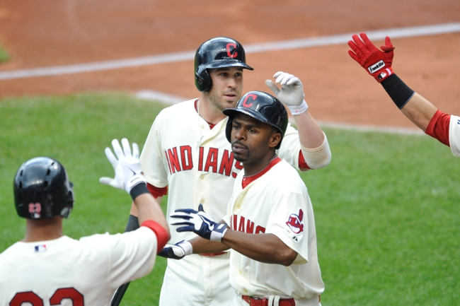 Jul 14, 2013; Cleveland, OH, USA; Cleveland Indians second baseman Jason Kipnis (second from left) is congratulated after scoring center fielder Michael Bourn (right) on a sacrifice fly ball in the first inning against the Kansas City Royals at Progressive Field. Mandatory Credit: David Richard-USA TODAY Sports