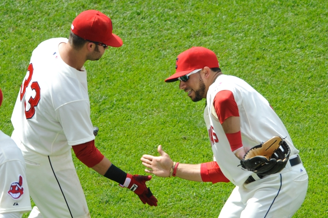Jul 14, 2013; Cleveland, OH, USA; Cleveland Indians first baseman Nick Swisher (33) and shortstop Mike Aviles (4) celebrate a 6-4 win over the Kansas City Royals at Progressive Field. Mandatory Credit: David Richard-USA TODAY Sports