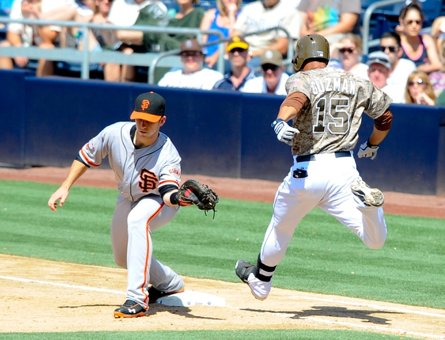 Jul 14, 2013; San Diego, CA, USA; San Francisco Giants first baseman Buster Posey (28) makes a play at first base ahead of San Diego Padres first baseman Jesus Guzman (15) during the sixth inning at Petco Park. Mandatory Credit: Christopher Hanewinckel-USA TODAY Sports