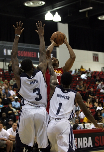 Jul 14, 2013; Las Vegas, NV, USA; Cleveland Cavaliers guard Cory Higgins attempts to take a shot over Memphis Grizzlies center Willie Reed and guard Tony Wroten during an NBA Summer League game at Cox Pavillion. Cleveland won the game 69-58. Mandatory Credit: Stephen R. Sylvanie-USA TODAY Sports