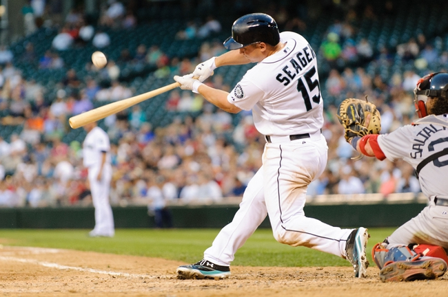 Jul 9, 2013; Seattle, WA, USA; Seattle Mariners third baseman Kyle Seager (15) hits the ball against the Boston Red Sox during the game at Safeco Field. Boston defeated Seattle 11-8. Mandatory Credit: Steven Bisig-USA TODAY Sports