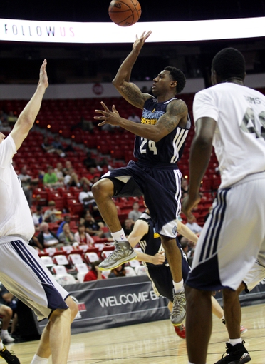 Jul 18, 2013; Las Vegas, NV, USA; Memphis Grizzlies guard Gerald Robinson floats the ball to the basket while splitting the defense of  Charlotte Bobcats forward Cody Zeller, left, and center Henry Sims during an NBA Summer League game at the Thomas and Mack Center. Mandatory Credit: Stephen R. Sylvanie-USA TODAY Sports