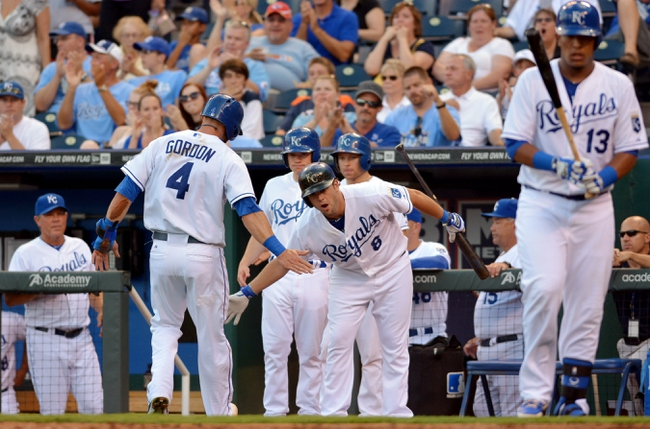 Jul 19, 2013; Kansas City, MO, USA; Kansas City Royals left fielder Alex Gordon (4) is congratulated by third baseman Mike Moustakas (8) after Gordon scores in the first inning of the game against the Detroit Tigers at Kauffman Stadium. Mandatory Credit: Denny Medley-USA TODAY Sports