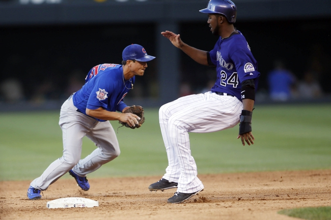Jul 20, 2013; Denver, CO, USA; Colorado Rockies center fielder Dexter Fowler (24) reaches second base before Chicago Cubs second baseman Darwin Barney (left) can make the tag during the third inning at Coors Field. Mandatory Credit: Chris Humphreys-USA TODAY Sports
