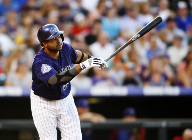 Jul 20, 2013; Denver, CO, USA; Colorado Rockies catcher Wilin Rosario (20) hits a double during the fourth inning against the Chicago Cubs at Coors Field. Mandatory Credit: Chris Humphreys-USA TODAY Sports