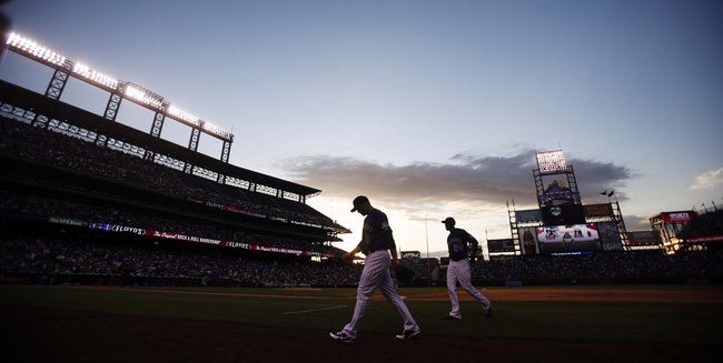 Jul 20, 2013; Denver, CO, USA; Colorado Rockies right fielder Michael Cuddyer (3) and center fielder Dexter Fowler (24) walk off the field during the fifth inning against the Chicago Cubs at Coors Field. Mandatory Credit: Chris Humphreys-USA TODAY Sports