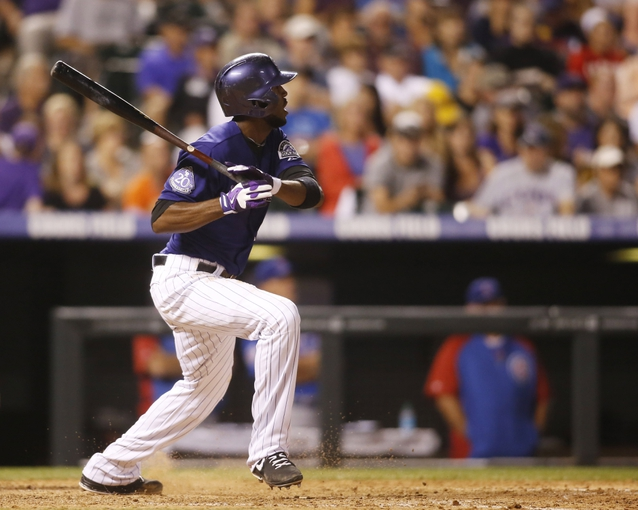Jul 20, 2013; Denver, CO, USA; Colorado Rockies center fielder Dexter Fowler (24) hits a single during the eighth inning against the Chicago Cubs at Coors Field. Mandatory Credit: Chris Humphreys-USA TODAY Sports