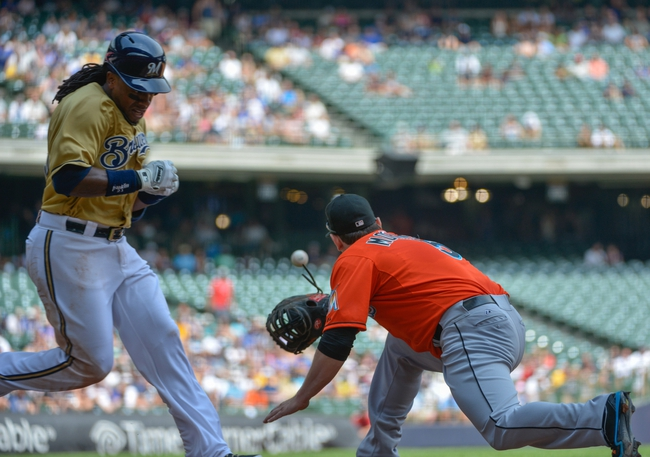 Jul 21, 2013; Milwaukee, WI, USA;  Milwaukee Brewers second baseman Rickie Weeks (left) is called out on a play to Miami Marlins first baseman Logan Morrison (right) in the 4th inning at Miller Park. Mandatory Credit: Benny Sieu-USA TODAY Sports