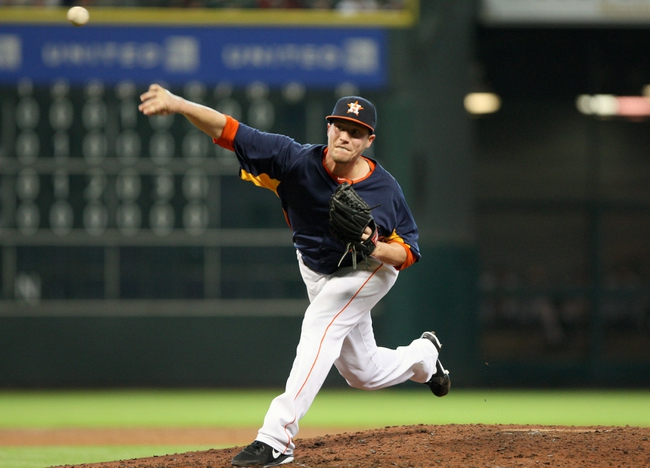 Jul 21, 2013; Houston, TX, USA; Houston Astros pitcher Lucas Harrell (64) delivers a pitch during the sixth inning against the Seattle Mariners at Minute Maid Park. Mandatory Credit: Troy Taormina-USA TODAY Sports
