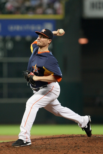 Jul 21, 2013; Houston, TX, USA; Houston Astros starting pitcher Lucas Harrell (64) pitches during the fifth inning against the Seattle Mariners at Minute Maid Park. Mandatory Credit: Troy Taormina-USA TODAY Sports