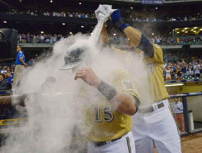 Jul 21, 2013; Milwaukee, WI, USA;  Milwaukee Brewers left fielder Caleb Gindl (15) is doused with powder by center fielder Carlos Gomez after Gindl's walkoff home run in the 13th inning against the Miami Marlins at Miller Park. The Brewers beat the Marlins 1-0.  Mandatory Credit: Benny Sieu-USA TODAY Sports