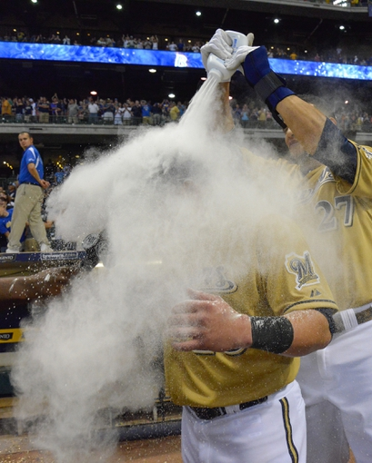 Jul 21, 2013; Milwaukee, WI, USA;  Milwaukee Brewers left fielder Caleb Gindl (left) is doused with powder by center fielder Carlos Gomez after Gindl's walkoff home run in the 13th inning against the Miami Marlins at Miller Park. The Brewers beat the Marlins 1-0.  Mandatory Credit: Benny Sieu-USA TODAY Sports