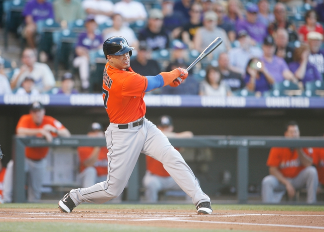 Jul 22, 2013; Denver, CO, USA; Miami Marlins right fielder Giancarlo Stanton (27) hits an RBI double during the first inning against the Colorado Rockies at Coors Field. Mandatory Credit: Chris Humphreys-USA TODAY Sports