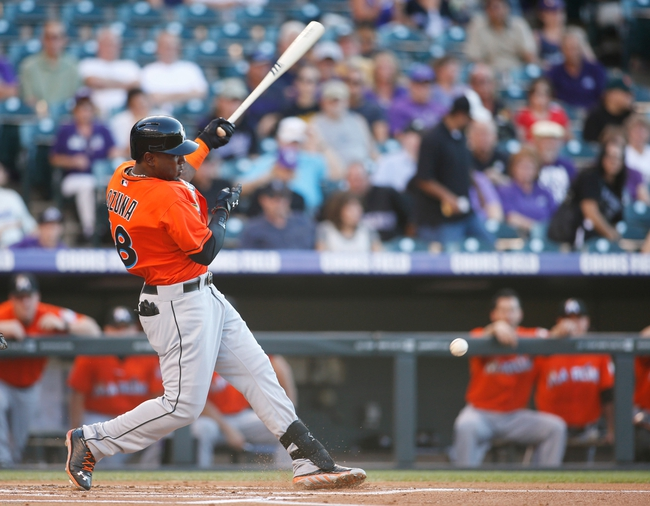 Jul 22, 2013; Denver, CO, USA; Miami Marlins center fielder Marcell Ozuna (48) hits a single during the first inning against the Colorado Rockies at Coors Field. Mandatory Credit: Chris Humphreys-USA TODAY Sports