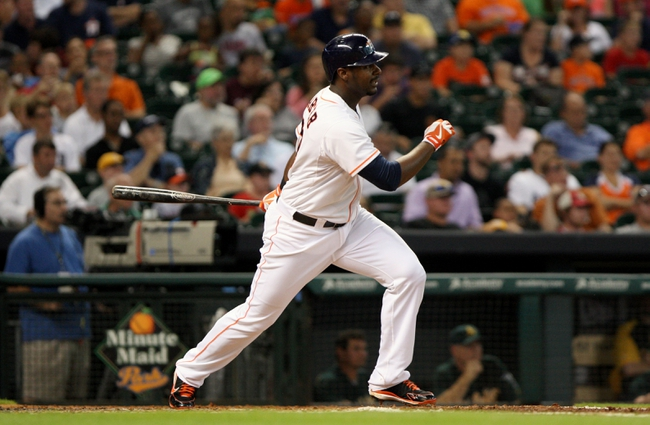 Jul 22, 2013; Houston, TX, USA; Houston Astros first baseman Chris Carter (23) drives in a run with a single during the third inning against the Oakland Athletics at Minute Maid Park. Mandatory Credit: Troy Taormina-USA TODAY Sports