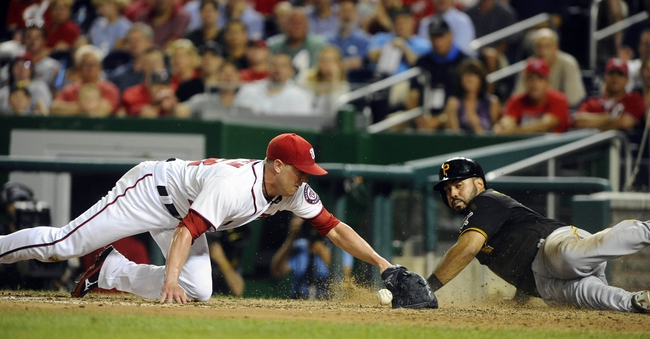 Jul 22, 2013; Washington, DC, USA; Pittsburgh Pirates first baseman Pedro Alvarez (24) scores on a wild pitch by Washington Nationals relief pitcher Drew Storen (22) during the eighth inning at Nationals Park. Mandatory Credit: Brad Mills-USA TODAY Sports