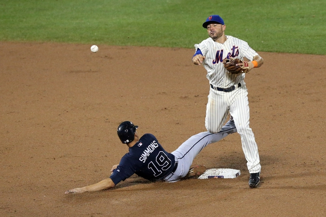 Jul 22, 2013; New York, NY, USA;  New York Mets shortstop Omar Quintanilla (3) has Atlanta Braves shortstop Andrelton Simmons (19) out at second but fails to complete the double play during the eighth inning at Citi Field.  Atlanta Braves won 2-1.  Credit: Anthony Gruppuso-USA TODAY Sports