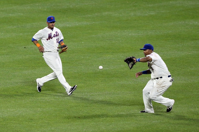 Jul 22, 2013; New York, NY, USA;  New York Mets right fielder Marlon Byrd (6) fields a ball as center fielder Juan Lagares (12) closes in to assist during the ninth inning against the Atlanta Braves at Citi Field.  Atlanta Braves won 2-1.  Credit: Anthony Gruppuso-USA TODAY Sports