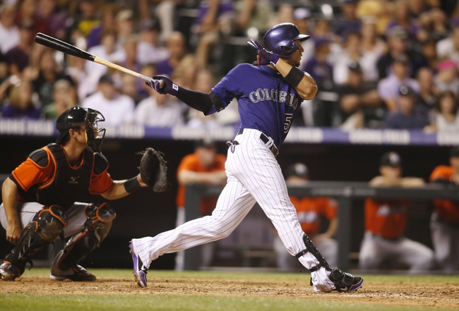 Jul 22, 2013; Denver, CO, USA; Colorado Rockies left fielder Carlos Gonzalez (5) hits a double during the eighth inning against the Miami Marlins at Coors Field. Mandatory Credit: Chris Humphreys-USA TODAY Sports