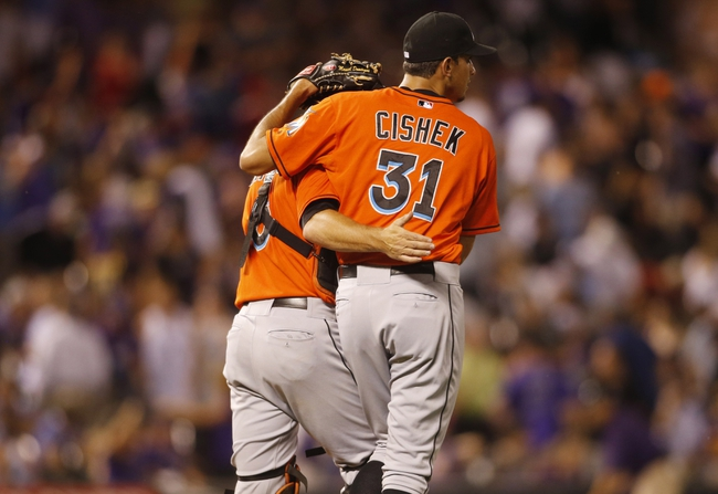 Jul 22, 2013; Denver, CO, USA; Miami Marlins pitcher Steve Cishek (31) is greeted by catcher Jeff Mathis (left) after the eighth inning against the Colorado Rockies at Coors Field. The Marlins won 3-1. Mandatory Credit: Chris Humphreys-USA TODAY Sports