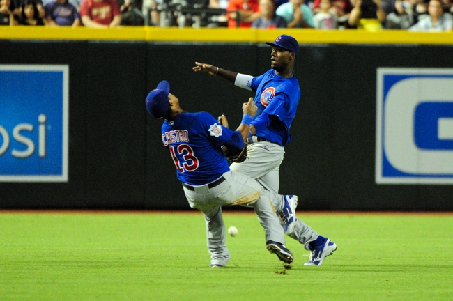 Jul 22, 2013; Phoenix, AZ, USA;  Chicago Cubs shortstop Starlin Castro (13) and shortstop Junior Lake (21) collide and miss catching the ball during the sixth inning at Chase Field. Mandatory Credit: Matt Kartozian-USA TODAY Sports