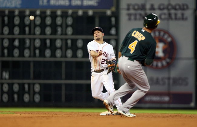 Jul 23, 2013; Houston, TX, USA; Oakland Athletics center fielder Coco Crisp (4) is out as Houston Astros second baseman Jose Altuve (27) throws to first base during the fifth inning at Minute Maid Park. Mandatory Credit: Troy Taormina-USA TODAY Sports