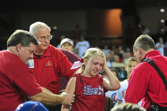 Jul 23, 2013; Phoenix, AZ, USA; A young fan receives help from medical staff after being hit in the head with a flying bat during the eighth inning of the game between the Arizona Diamondbacks and the Chicago Cubs at Chase Field. Mandatory Credit: Matt Kartozian-USA TODAY Sports