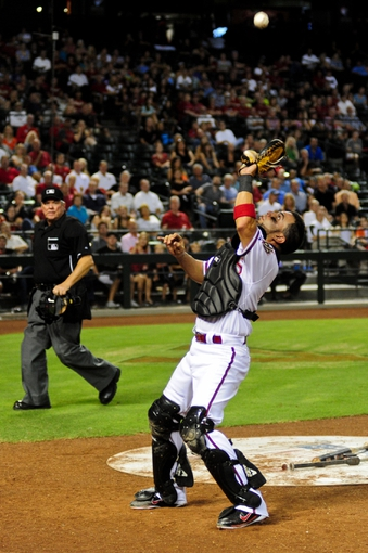 Jul 23, 2013; Phoenix, AZ, USA; Arizona Diamondbacks catcher Wil Nieves (27) catches a foul ball during the eighth inning against the Chicago Cubs at Chase Field. Mandatory Credit: Matt Kartozian-USA TODAY Sports