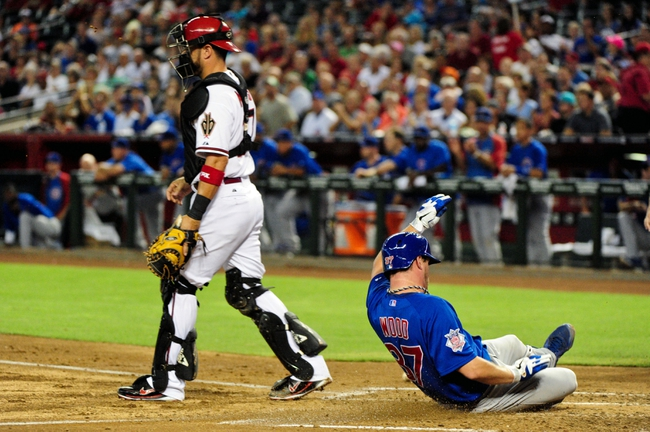 Jul 23, 2013; Phoenix, AZ, USA; Chicago Cubs starting pitcher Travis Wood (37) scores on a single by first baseman Anthony Rizzo (not pictured) as Arizona Diamondbacks catcher Wil Nieves (27) waits for the ball during the third inning at Chase Field. Mandatory Credit: Matt Kartozian-USA TODAY Sports