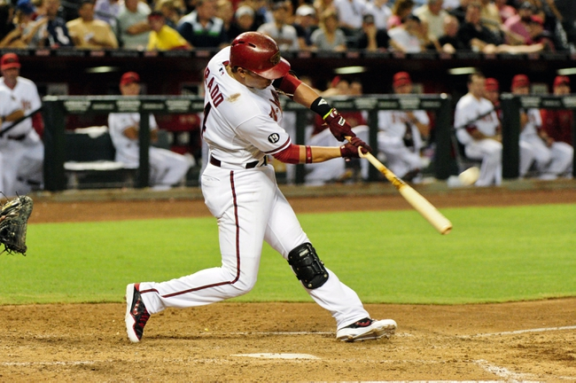 Jul 23, 2013; Phoenix, AZ, USA; Arizona Diamondbacks third baseman Martin Prado (14) hits a solo home run during the fifth inning against the Chicago Cubs at Chase Field. Mandatory Credit: Matt Kartozian-USA TODAY Sports