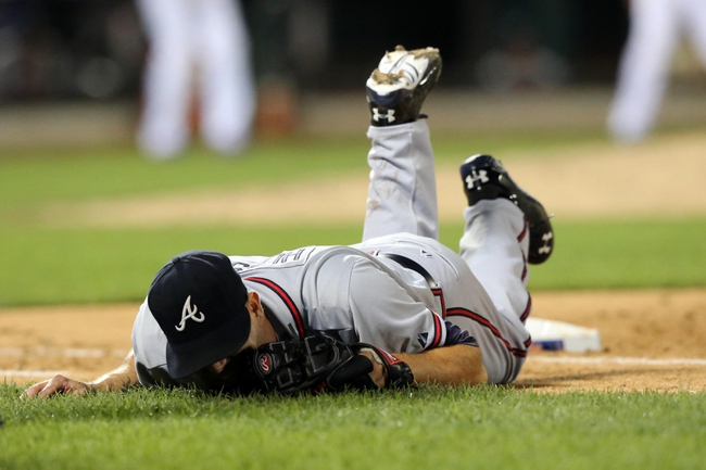 Jul 24, 2013; New York, NY, USA;  Atlanta Braves starting pitcher Tim Hudson (15) is injured in collision at first base with New York Mets left fielder Eric Young Jr. (not pictured) during the eighth inning at Citi Field. Mandatory Credit: Anthony Gruppuso-USA TODAY Sports