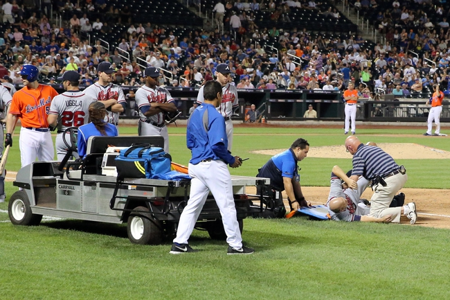 Jul 24, 2013; New York, NY, USA;  Atlanta Braves starting pitcher Tim Hudson (15) is taken from the field after being injured in collision at first base with New York Mets left fielder Eric Young Jr. (not pictured) during the eighth inning at Citi Field. Mandatory Credit: Anthony Gruppuso-USA TODAY Sports