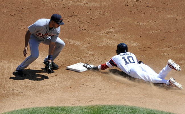 Jul 25, 2013; Chicago, IL, USA; Chicago White Sox shortstop Alexei Ramirez (10) steals second base as Detroit Tigers shortstop Jhonny Peralta (27) makes a late tag during the first inning at U. S. Cellular Field. Mandatory Credit: David Banks-USA TODAY Sports