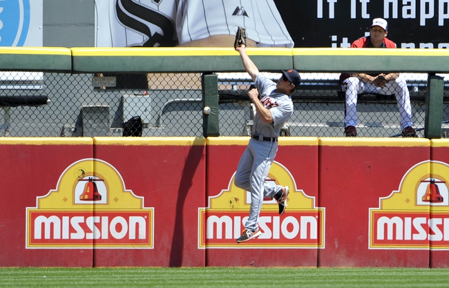 Jul 25, 2013; Chicago, IL, USA; Detroit Tigers left fielder Andy Dirks (12) cannot make a catch on a double off the bat of Chicago White Sox third baseman Conor Gillaspie (not pictured) during the second inning at U.S. Cellular Field. Mandatory Credit: David Banks-USA TODAY Sports