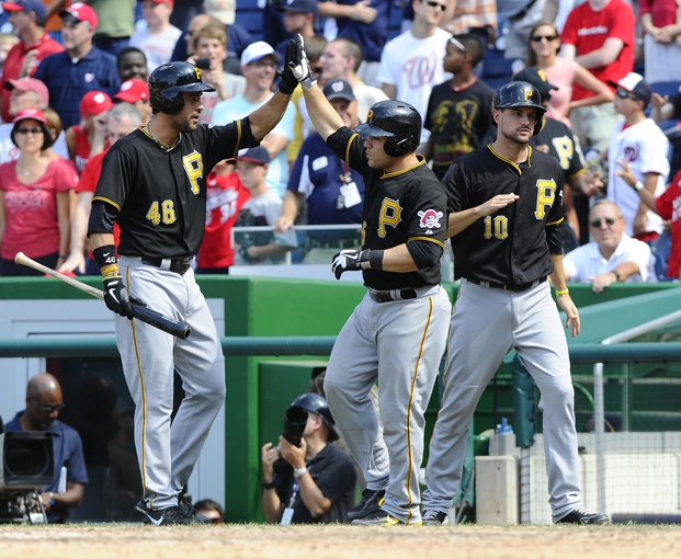 Jul 25, 2013; Washington, DC, USA; Pittsburgh Pirates catcher Russell Martin (55) is congratulated by Garrett Jones (46) and Jordy Mercer (10) after scoring a run during the ninth inning against the Washington Nationals at Nationals Park.  Mandatory Credit: Brad Mills-USA TODAY Sports
