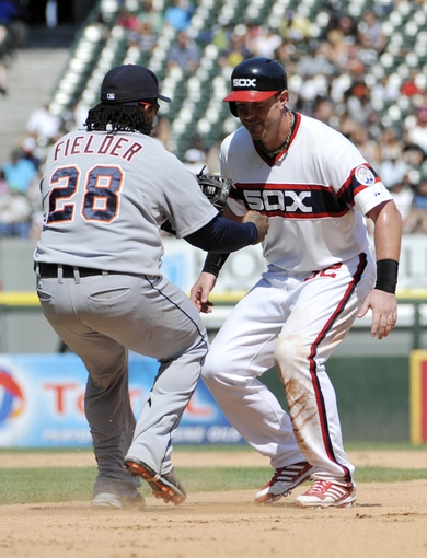 Jul 25, 2013; Chicago, IL, USA; Chicago White Sox first baseman Adam Dunn (32) is tagged out by Detroit Tigers first baseman Prince Fielder (28) after being picked off during the seventh inning at U.S. Cellular Field. The Chicago White Sox defeated the Detro