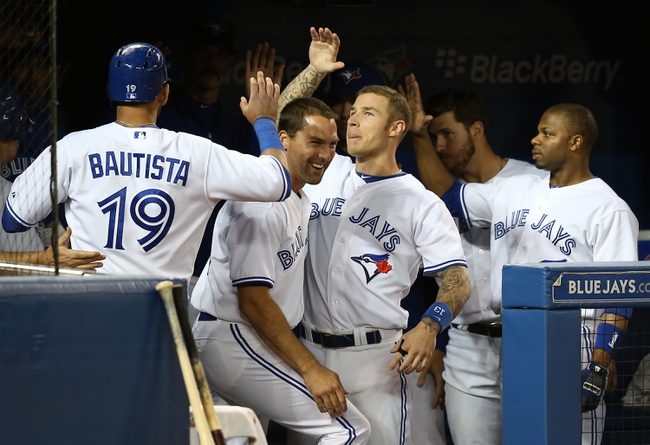 Jul 25, 2013; Toronto, Ontario, CAN; Toronto Blue Jays right fielder Jose Bautista (19) celebrates after scoring a run in the seventh inning with third baseman Brett Lawrie (13) and designated hitter Mark DeRosa (16) against the Houston Astros at Rogers Centre. Mandatory Credit: Tom Szczerbowski-USA TODAY Sports