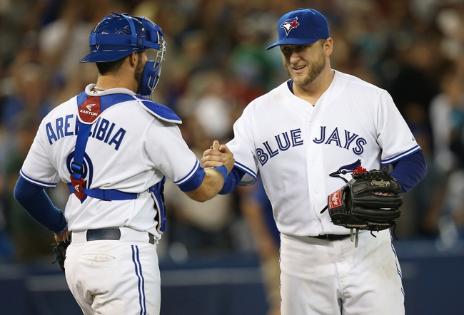 Jul 25, 2013; Toronto, Ontario, CAN; Toronto Blue Jays starting pitcher Mark Buehrle (56) celebrates his complete-game victory with catcher J.P. Arencibia (9) against the Houston Astros at Rogers Centre. The Blue Jays beat the Astros 4-0. Mandatory Credit: Tom Szczerbowski-USA TODAY Sports