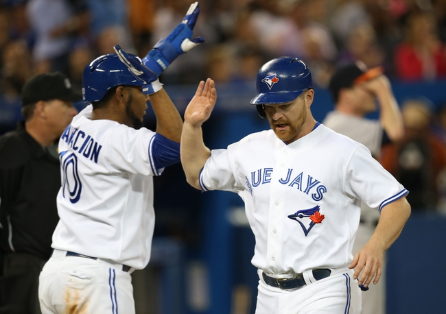 Jul 25, 2013; Toronto, Ontario, CAN; Toronto Blue Jays pinch hitter Adam Lind (26) is congratulated by first baseman Edwin Encarnacion (10) after scoring a run in the seventh inning against the Houston Astros at Rogers Centre. The Blue Jays beat the Astros 4-0. Mandatory Credit: Tom Szczerbowski-USA TODAY Sports