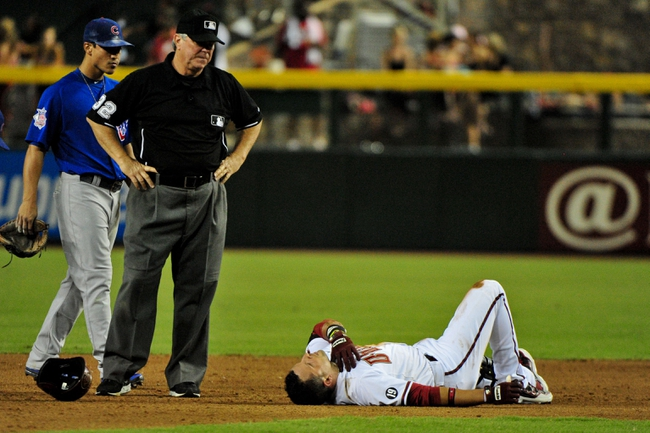 Jul 25, 2013; Phoenix, AZ, USA; Arizona Diamondbacks third baseman Martin Prado (14) lays hurt on the first after colliding with Chicago Cubs shortstop Starlin Castro (13) during the fifth inning at Chase Field. Mandatory Credit: Matt Kartozian-USA TODAY Sports