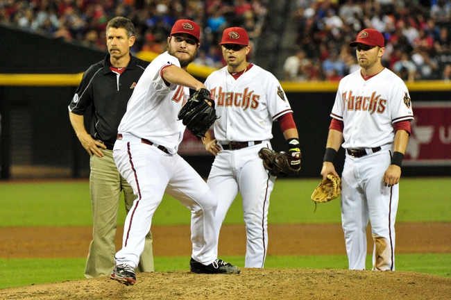 Jul 25, 2013; Phoenix, AZ, USA; Arizona Diamondbacks starting pitcher Wade Miley (36) throws a warm up pitch after being hit by a line drive as teammates and a trainer look on during the third inning against the Chicago Cubs at Chase Field. Mandatory Credit: Matt Kartozian-USA TODAY Sports