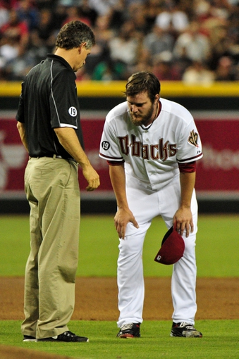 Jul 25, 2013; Phoenix, AZ, USA; Medical staff attends to Arizona Diamondbacks starting pitcher Wade Miley (36) after bring hit by a line drive from Chicago Cubs catcher Welington Castillo (53) during the third inning at Chase Field. Mandatory Credit: Matt Kartozian-USA TODAY Sports