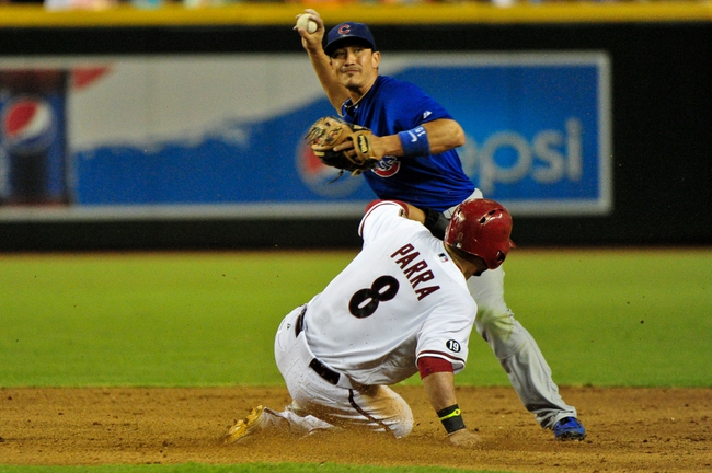 Jul 25, 2013; Phoenix, AZ, USA; Chicago Cubs second baseman Darwin Barney (15) turns a double play as Arizona Diamondbacks right fielder Gerardo Parra (8) slides during the eighth inning at Chase Field. Mandatory Credit: Matt Kartozian-USA TODAY Sports