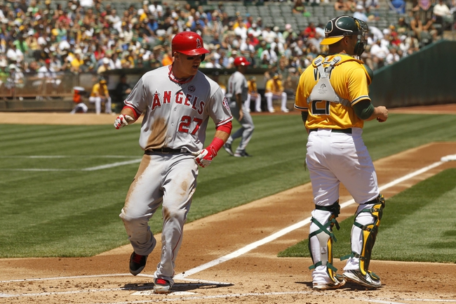 Jul 28, 2013; Oakland, CA, USA; Los Angeles Angels outfielder Mike Trout (27) scores a run next to Oakland Athletics catcher Stephen Vogt (21)  in the first inning at O.co Coliseum. Mandatory Credit: Cary Edmondson-USA TODAY Sports