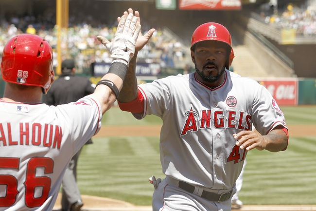 Jul 28, 2013; Oakland, CA, USA; Los Angeles Angels infielder Howie Kendrick (47) is congratulated by outfielder Kole Calhoun (56) after scoring a run against the Oakland Athletics in the first inning at O.co Coliseum. Mandatory Credit: Cary Edmondson-USA TODAY Sports