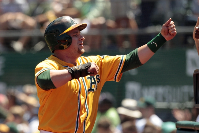 Jul 28, 2013; Oakland, CA, USA; Oakland Athletics catcher Stephen Vogt (21) is congratulated by teammates after scoring a run against the Los Angeles Angels in the third inning at O.co Coliseum. Mandatory Credit: Cary Edmondson-USA TODAY Sports