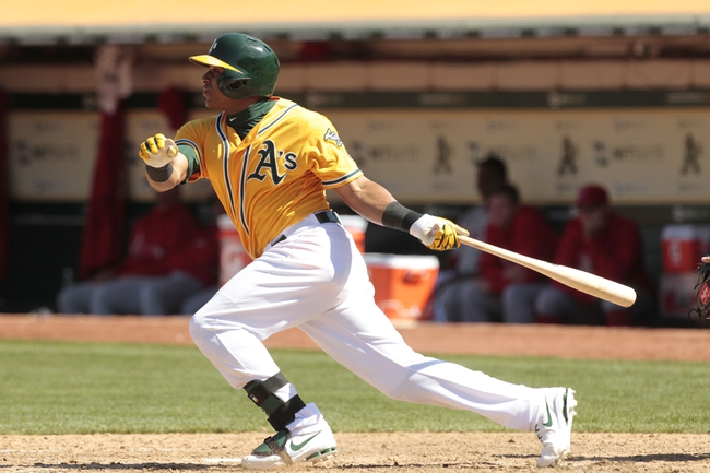 Jul 28, 2013; Oakland, CA, USA; Oakland Athletics outfielder Yoenis Cespedes (52) hits a two-run double against the Los Angeles Angels in the sixth inning at O.co Coliseum. Mandatory Credit: Cary Edmondson-USA TODAY Sports
