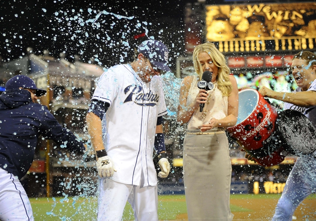 Jul 29, 2013; San Diego, CA, USA; San Diego Padres pinch hitter Chris Denorfia (13) is dumped with Powerade by catcher Nick Hundley (right) during a post-game interview with Fox Sports San Diego reporter Kelly Crull following a walk off two-run home run in the ninth inning inning against the Cincinnati Reds at Petco Park. . Mandatory Credit: Christopher Hanewinckel-USA TODAY Sports